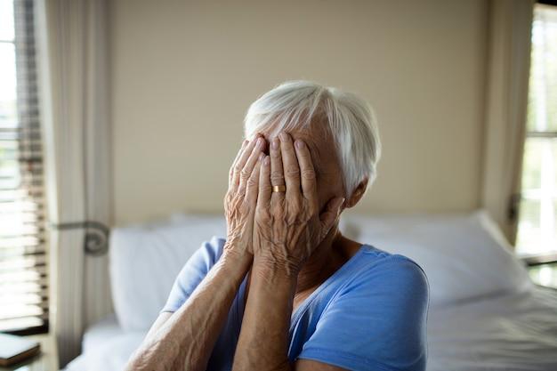 Beklemtoonde hogere vrouw die haar gezicht behandelt met handen thuis