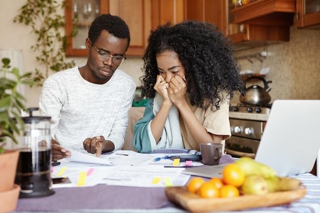 Beklemtoonde jonge afrikaanse vrouw hand in hand op haar gezicht, wanhopig luisterend naar haar man die de melding leest en informeert dat ze hun appartement moeten verlaten vanwege niet-betaling