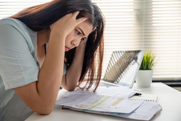Beklemtoonde jonge aziatische vrouw geen geld om schuld te betalen die maandelijkse uitgavenrekeningen op lijst kijken
