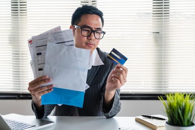Beklemtoonde jonge aziatische zakenman die zoveel elektriciteitsrekeningen houdt