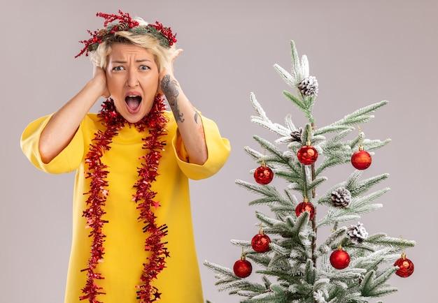 Beklemtoonde jonge blonde vrouw die de hoofdkroon van kerstmis en klatergoudslinger om hals draagt staand dichtbij versierde kerstboom kijkend handen op het hoofd houdend schreeuwend geïsoleerd op witte muur