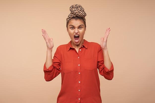 Beklemtoonde jonge bruinharige vrouw met natuurlijke make-up die emotioneel haar handen opheft tijdens het kijken naar voorzijde met geïrriteerd gezicht, staande over beige muur