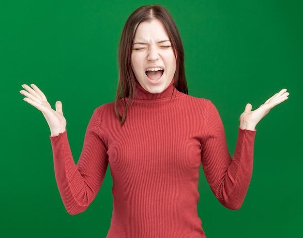 Beklemtoonde jonge mooie vrouw die lege handen toont die met gesloten ogen schreeuwen die op groene muur worden geïsoleerd