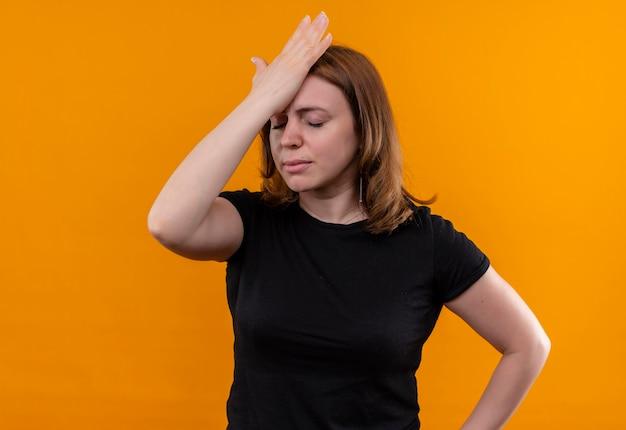 Beklemtoonde jonge toevallige vrouw die hand op hoofd met gesloten ogen op geïsoleerde oranje muur met exemplaarruimte zet
