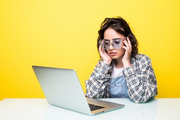 Beklemtoonde jonge vrouw die aan geïsoleerde laptop werkt