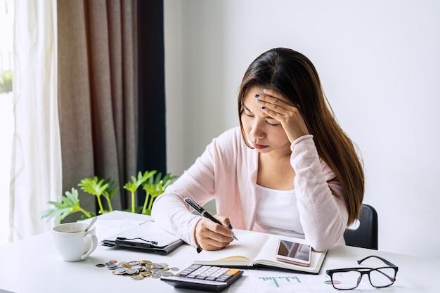 Beklemtoonde jonge vrouw die maandelijkse huiskosten, belastingen, het saldo van de bankrekening en de betaling van creditcardrekeningen berekent