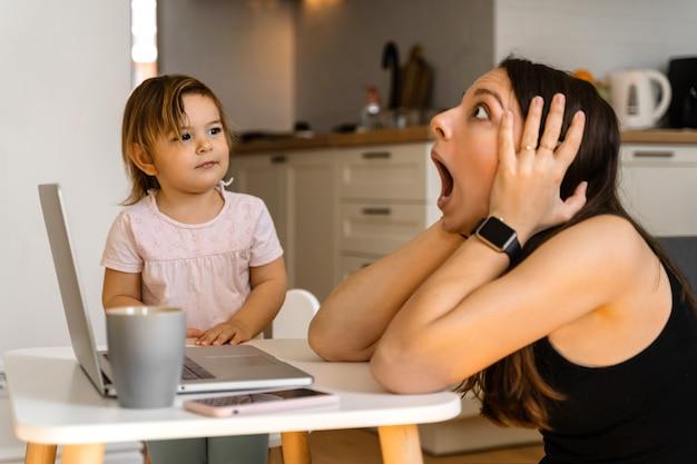 Beklemtoonde jonge vrouw die van huis met klein kind werkt. thuiskantoor van alleenstaande moeder