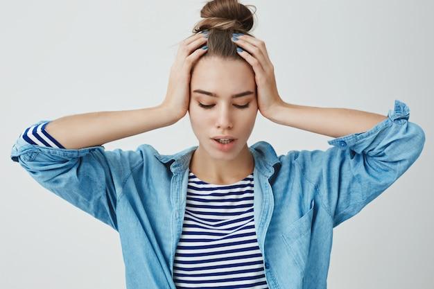 Beklemtoonde jonge vrouw met beide handen op hoofd