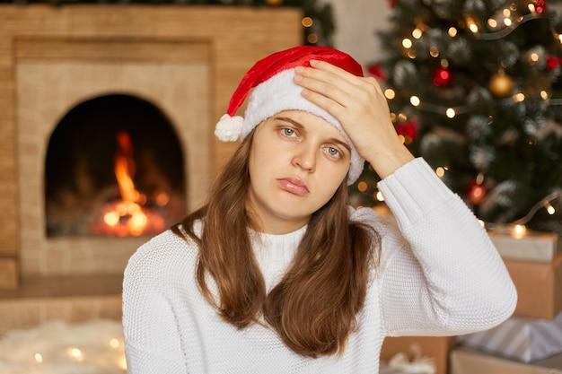 Beklemtoonde kerstmisvrouw die hoofdpijn heeft