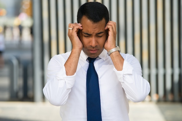 Beklemtoonde latijnse zakenman holding head with hands