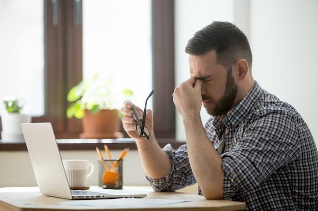 Beklemtoonde mannelijke masserende neusbrug die aan hoofdpijn lijdt