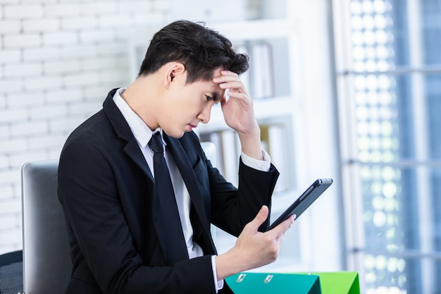 Beklemtoonde mens die met een tablet werkt