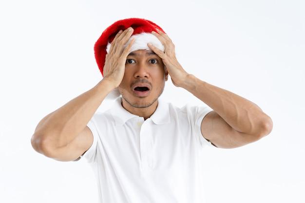 Beklemtoonde mens die santa claus-hoed en clutching hoofd draagt