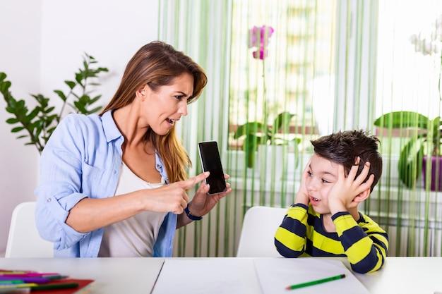 Beklemtoonde moeder en zoon gefrustreerd over mislukkingsthuiswerk, het concept van schoolproblemen.