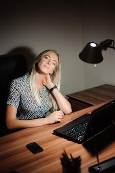 Beklemtoonde onderneemsterzitting bij bureau en het denken van de oplossing terwijl laat het werken voor een computer.