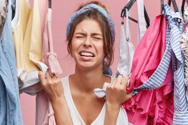Beklemtoonde ongelukkige jonge europese vrouw die stijlvolle kleding aanraakt en hardop schreeuwt omdat ze die niet kan betalen. gefrustreerde vrouw met een trieste en pijnlijke blik omdat ze niets te dragen heeft