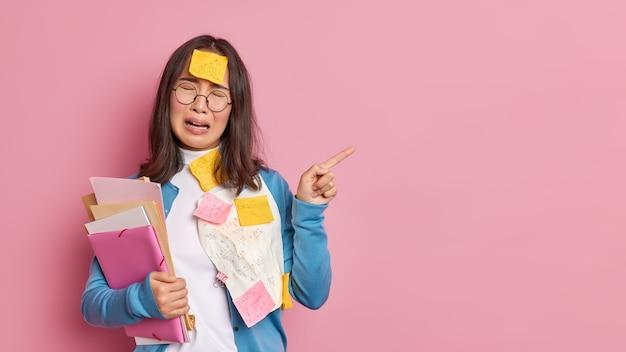 Beklemtoonde ongelukkige vrouwelijke student huilt van wanhoop die het beu is van examenvoorbereiding wijst weg op een lege ruimte die overladen is met papieren, moet veel informatie onthouden.