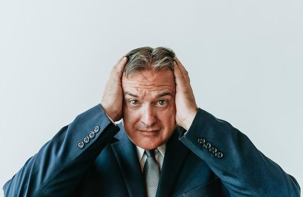 Beklemtoonde oude zakenman die zijn hoofd aanraakt
