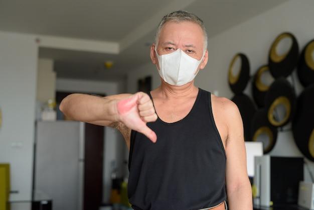 Beklemtoonde rijpe japanse mens met masker die duimen thuis onder quarantaine geven wegens covid-19 pandemie