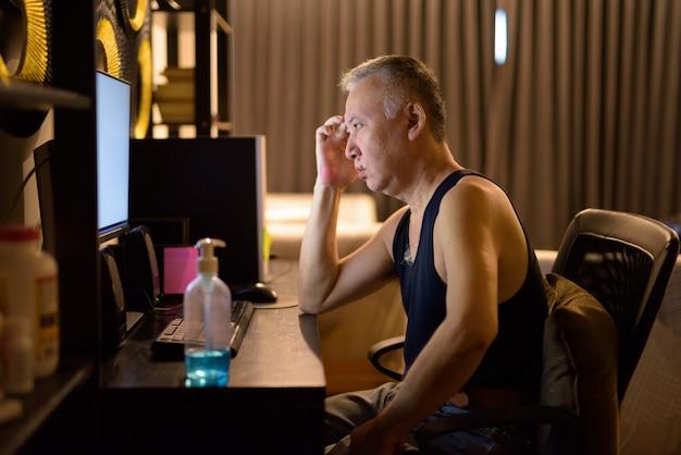 Beklemtoonde rijpe japanse mens thuis gebruikend computer en hebbend hoofdpijn