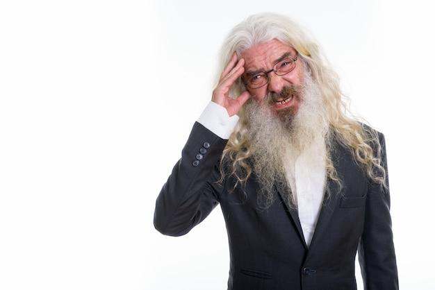 Beklemtoonde senior bebaarde zakenman met hoofdpijn