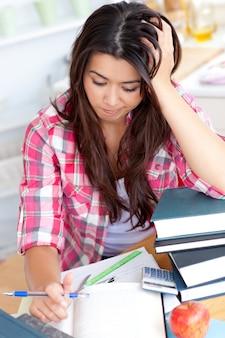 Beklemtoonde student die haar thuiswerk doet