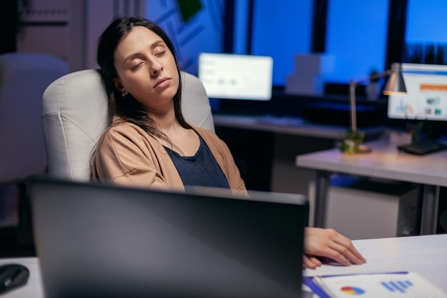 Beklemtoonde vermoeide zakenvrouw die in een leeg kantoor slaapt tijdens overuren. werknemer valt in slaap terwijl hij 's avonds laat alleen op kantoor werkt voor een belangrijk bedrijfsproject.