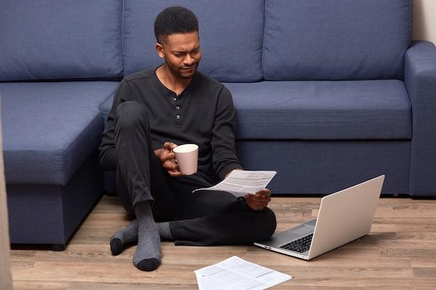Beklemtoonde verstoorde mensenzitting op vloerholding nam kop met drank en document in beide handen toe, aandachtig lezend, gebruikend zijn laptop