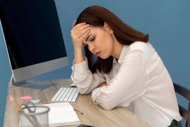 Beklemtoonde vrouw die aan computer werkt