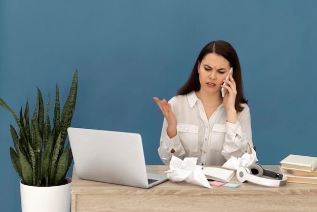 Beklemtoonde vrouw die aan laptop werkt