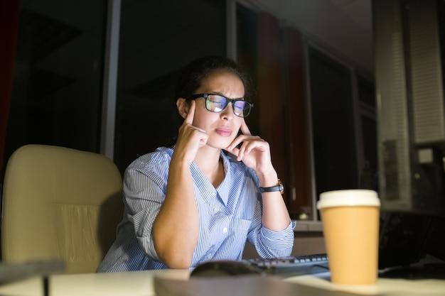 Beklemtoonde vrouw die bij nacht werkt