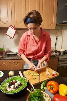 Beklemtoonde vrouw die een gezonde salade voorbereidt