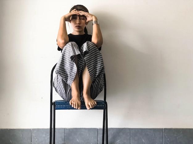 Beklemtoonde vrouwenzitting met een hoge knie op stoel, met verstoord en ongelukkig gevoel, depressieve stoornis syndroom, ernstige emotie