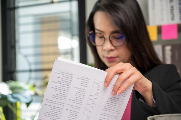 Beklemtoonde werkende vrouw aan het bureau in een bedrijfskantoor