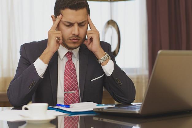 Beklemtoonde zakenman die aan zijn laptop werkt