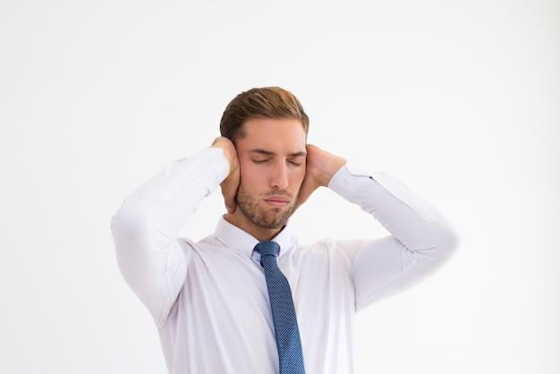 Beklemtoonde zakenman die oren behandelt met handen