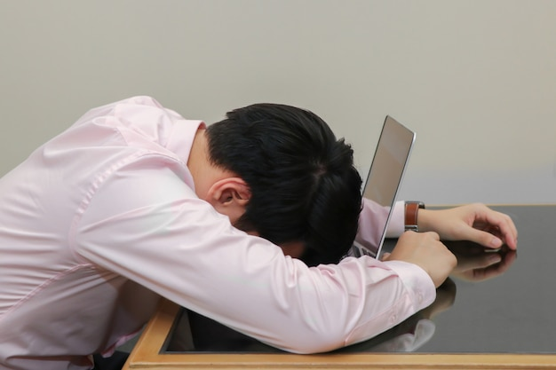 Beklemtoonde zakenmanslaap op zijn laptop met burnout syndroom