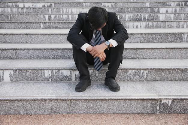 Beklemtoonde zakenmanzitting bij trap openlucht. bankrupt zakenmanzitting openlucht