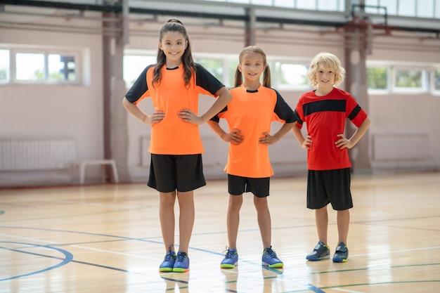 Bekrachtigd. kinderen in lichte sportkleding staan met de handen op de heupen