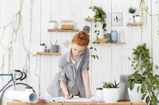 Bekwame aantrekkelijke roodharige europese vrouw architect bezig met het maken van aantekeningen