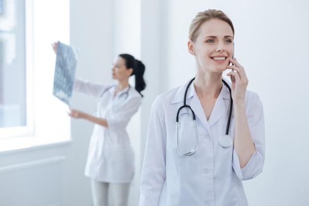 Bekwame blij volwassen neuroloog werken in het medische lab en genieten van een gesprek op de smartphone terwijl haar collega x-ray beeld van de hersenen houdt en analyseert
