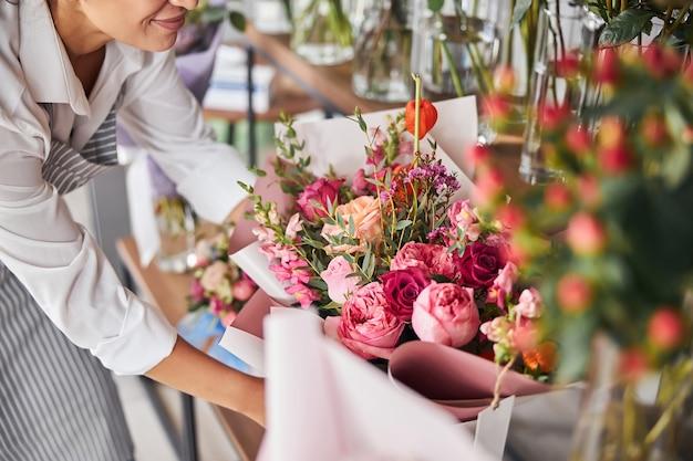 Bekwame bloemist zet kant-en-klare boeketten op een plank