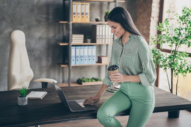 Bekwame dame deskundige met behulp van laptop zitten op tafel op kantoor