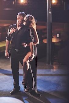 Bekwame dansers die in een donkere kamer onder licht presteren.