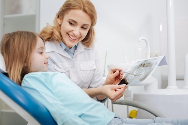 Bekwame, ervaren pediatrische tandarts die haar kleine geduldige röntgenfoto van haar tanden laat zien en uitlegt hoeveel haar gebitgezondheid verbetert