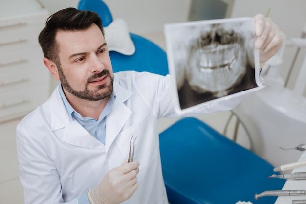 Bekwame ervaren prominente tandarts die röntgenfoto's van de tanden van zijn patiënten bestudeert terwijl hij de diagnose uitzoekt voordat een behandeling wordt gestart
