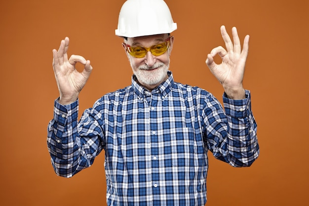 Bekwame ervaren senior architect of industrieel inspecteur met grijze baard die goedkeuring uitdrukt, goed gebaar maakt, kijkt met een stralende glimlach. beroep, baan, beroep en leeftijd
