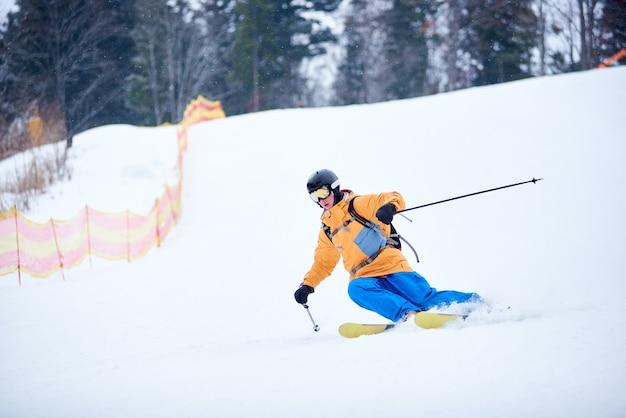 Bekwame jonge skiër concentreerde zich op skiën op een steile skipiste. extreme winteractiviteiten concept. vooraanzicht