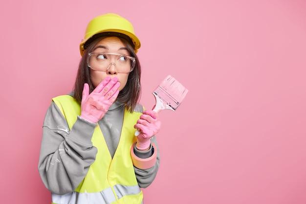 Bekwame jonge vrouwelijke schilder bedekt mond met hand geconcentreerd weg houdt schilderborstel vast
