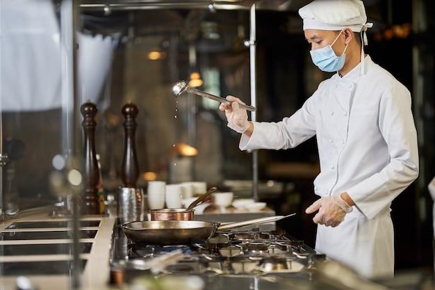 Bekwame kok in gezichtsmasker die pollepel boven een pan houdt
